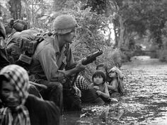 Two South Vietnamese children gaze at an American paratrooper holding a grenade launcher as they cling to their mothers who huddle against a canal bank for protection from Viet Cong sniper fire in the Bao Trai area, Vietnam.