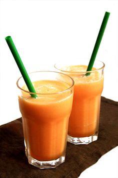 Due bicchieri di frullato di melone e sedano con due cannucce verdi sopra un tovagliolo marrone su sfondo bianco