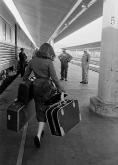 Young stylish women with three suitcases on a train station platform. Engineer and conductors observing. #Vintage #travel #railways