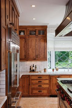 in love with this rustic cabinetry (wormy chestnut?), tudor windows, white brick, love love love