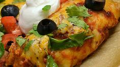 Ground beef enchiladas in flour tortillas topped with spicy red sauce, cheese and fresh cilantro is so flavorful!  It takes time and effort, but well worth it!  Serve with Mexican rice and beans for a complete Mexican meal.