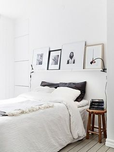 shelf with two black clip lights; dark grey pillowcases behind two white. i like how the bedding reaches the floor - is this just oversized? Decir for spare  bedroom
