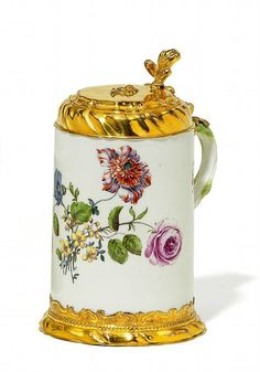 Tankard with splendid fire-gilded mounting, Meissen, ca. 1750 Porcelain, decorated in colours. Fire-gilded copper mountins. Plain cylindrical body with twig-shaped handle. On the front large floral bouquet as well as large scattered blossoms. Height 20,5 cm