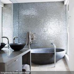 Eine Wand voller verspiegelter Mosaikfliesen im Bad ist ein Hingucker. Die reliefartige Struktur der Mosaikfliesen gibt der Wand eine spannende Dynamik. - mehr auf roomido.com
