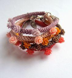 Estas sencillas pulseras están hechas con rafia blanca teñida y con piezas pequeñas de resina de flores de colores que van i...