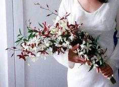 over the arm bouquet of white dendrobium orchids and red oncidium