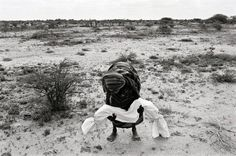 © James Nachtwey, Lifting a dead son to carry hom to a mass grave during the famine Somalia, 1992