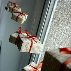 Love this idea—packages wrapped in book pages  & red ribbon, then hung as a mobile—a fabulous look❣