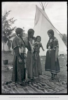 Enias Conkos family - generations admiring baby. Three Native American women stand, one holds a baby.  Photographed by Edward H. Boos circa 1900 - 1907