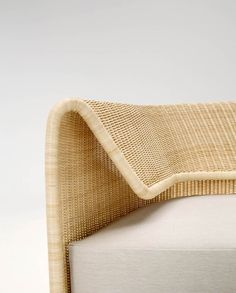 Wrap sofa's curved wicker backrest provides support and flex for comfort.