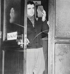 """Original caption: Can't Always Believe in Signs. Brooklyn, New York: Charles (The Bug) Workman would like to believe the """"This Way Out"""" sign on the door of the district attorney's office where he has questioned in the Dutch Schultz killing. Workman was shown the way out -- to the Butler Street police station where he is being held. (Copyright Bettmann/Corbis / AP Images)"""