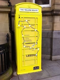 Yellow phone box showing Le Tour Yorkshire route outside Leeds Train Station...