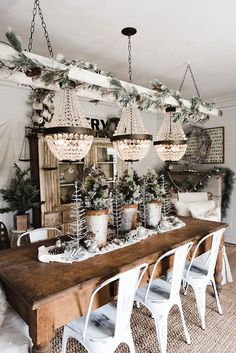 A little garland and natural Christmas decor go a long way when a trio of jaw-dropping chandeliers are a focal point in this cozy farmhouse.