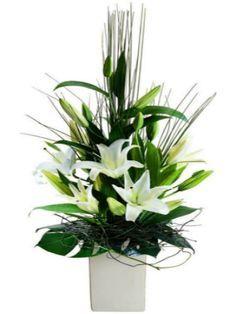 Arreglo floral con florero en porcelana de liliums y follaje verde