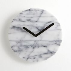 White marble disc shapes a clean, organic face to this contemporary clock, minimally detailed with bold, black hands and without numbers. Marble, clock movement and metalRequires one AA battery (not included)Clean with soft, dry clothMade in Taiwan.