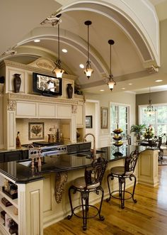 This luxe kitchen has a barrel vaulted ceiling, granite counterttops an eating area and even a television.... V
