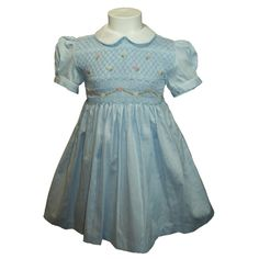 """Vikki (Blue) - Traditional smocked dress with embroidery overlay.  Styled with short """"cuff"""" sleeves and """"Peter Pan"""" collar. Button fastening at the back, with matching fabric """"ribbons"""" to tie a bow.  Fabric piping to collar and cuffs to compliment embroidery. Available in sizes 5-6 and 7-8 years."""