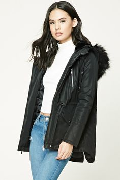 A woven parka featuring a drawstring hood with a faux fur lining, detachable faux fur trim on the hood, a zip front, drawstring waist, snap-button flap pockets, chest zip pockets, and a quilted padded lining.