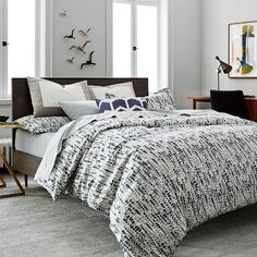 Bedding - Paying homage to textile designer, Lucienne Day, the Lucienne collection gives a nod to mid-century design in its truest form. The soft, abstract botanical print marries with a masculine shade of Blue and gray, for a balanced aesthetic. The subtle look of Lucienne allows it to effortlessly blend into a room, while the cotton fabric adorned with a brushstroke pattern brings a textural appearance to the collection.