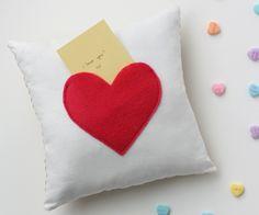 Una simple nota puede alegrar el día a cualquiera y más si ésta está en el interior de un corazón. ¡Tan sólo con una aguja, hilo y fieltro rojo o rosado, puedes hacer bolsillos en cojines y almohadas para crear un lindo portanotas! #ElRegaloIdeal #DIY