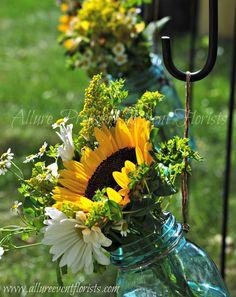 Vintage mason jars hanging on shepherds hooks with gorgeous sunflowers and daisies
