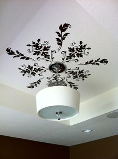 Another idea I would never have thought of - vinyl on the ceiling as a medallion around a light. If you aren't a vinyl person, stencils would achieve the same effect.