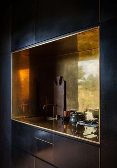 Two Tiny Cabins Chose Simplicity Over Size, The kitchen's brass-lined niche, with a matching tap by Arne Jacobsen for Vola, contrasts the otherwise spare, black formply interior of one of the ca. Black Kitchens, Luxury Kitchens, Cool Kitchens, Kitchen Black, Brass Kitchen, Mini Kitchen, Kitchen Sink, Kitchen Dining, Kitchen Decor