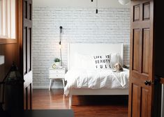 Iron, edison, and cloth cord complete this industrial minimalist bedroom. Exposed Brick Wallpaper, Black Brick Wallpaper, White Wash Brick, White Brick Walls, White Bricks, Industrial Wallpaper, How To Install Wallpaper, Industrial Style Lighting, Urban Decor