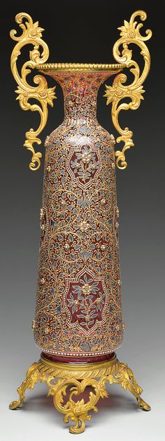 Moser monumental decorated glass vase with its massive cranberry body with all over enameled floral decoration and elaborate gilded brass handles, foot and collar.