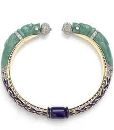 An Art Deco jadeite jade, enamel and diamond bangle bracelet, French, circa 1925. Rotating cuff bangle with carved jade dragon terminals; with French assay marks; mounted in eighteen karat gold and platinum; diameter: 2 1/2in.  #ArtDeco #bangle #bracelet