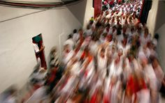 Runners enter the bullring during the third running of the bulls of the San Fermin festival, on July 9, 2012.