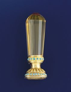 A early Victorian gold, citrine and turquoise desk seal  With faceted citrine handle, the foiled citrine intaglio in chased gold mount with engraved foliate and turquoise pellet decoration, the seal engraved with a kneeling slave in fetters, with the inscription 'on m'attache pour me tuer', circa 1830
