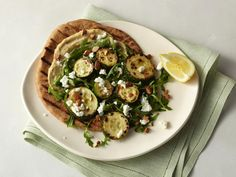 This pizza-like meatless Roasted Zucchini Flatbread comes together easily using store-bought pita and hummus, plus oven-roasted zucchini, lemon and goat cheese.