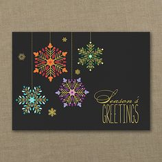 Four colorful snowflakes hang from above, contrasting very nicely with the black background of the card and accented with gold foil to match the 'Season's Greetings' message shown.    Made from recycled paper by manufacturers using renewable energy sources.