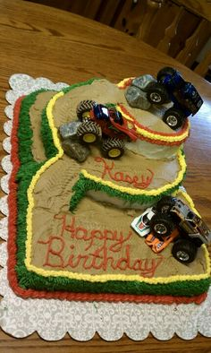 Monster truck cake like the sheet cake under for more space to decorate and the three teirs for trucks to climb, two trucks and five cars, add a banner at the top, and checkered flag, boys names and number five