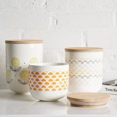 A delightful collection of simply shaped ceramic storage jars decorated with abstract retro-style patterns.This range of Scandinavian style retro kitchen canisters comes in three sizes to match your storage requirements and each have a distinctive pattern to match their size; - Small has a delicate orange fan flower pattern : £19.00 - Medium a multi-coloured geometric scales design : £24.00 - Large has big deconstructed yellow dandelions : £29.00 - A complete set of all thre...