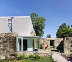 This house design inspired by stunning contrasts of vintage and modern ideas. The modern house is in Spain and called Generously Lit Single Family House. Modern living spaces and old stone walls strong character to this single family home.    The house is located in Pontevedra, Spain, harmoniously b