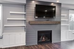Living Room: Pecan hardwood floors, painted shiplap gas fireplace surround with floating beam mantle, painted floating shelves and built-ins