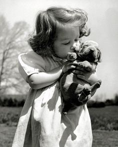 """""""Puppy love is evident as Christina Goldsmith, 2 ½, kisses a young acquaintance. The Weimaraner makes a good household pet and an excellent watchdog."""" - LIFE magazine, June 12, 1950. (Bernard..."""