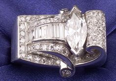 Retro Platinum and Diamond Ring, the scrolling mount prong-set with a marquise-cut diamond weighing approx. 1.40 cts., surrounded by baguette and old single-cut diamonds