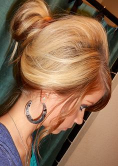 Medium length honey blonde hair with reddish-caramel lowlights or streaks set in a bumped out messy bun and loose curls on either side of the head. L♥Ve it!