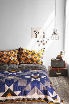Bed on the floor with a great suitcase side table.