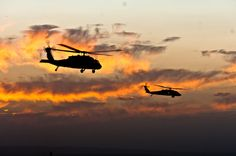 Two UH-60 Black Hawk helicopters hover over the skies of Spin Boldak, in the southern Kandahar province, Afghanistan, before flying away.