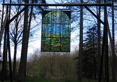 Stained glass window hanging in the woods - 'Cathedral'. Part of the Sculpture Trail in the Forest of Dean. Artist: Kevin Atherton, born in the Isle of Man.
