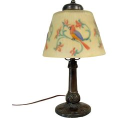 This nice reverse-painted electric boudoir lamp depicts blown-out parrots on branches with a floral design. It is ribbed all around with beautiful