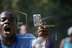A supporter of Haiti's former President Jean-Bertrand Aristide holds up a picture of him, while demonstrating in front of his house during a protest in his support, in Port-au-Prince, Haiti, Thursday, Aug. 21, 2014. Supporters of the former president have been blocking the street in front of his house as the popular former leader faces possible arrest for not providing court-ordered testimony in a criminal investigation. (AP Photo/Dieu Nalio Chery)
