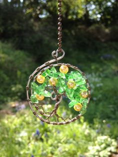 This beautiful handmade Tree of Life Lemon Tree Pendant is made from a twisted curled ring frame of galvanised steal wire, which ensures its strength and durability.  The inner Lemon Tree is made using twisted brown copper craft wire.  The leaves and fruit are made from chipped glass stones and yellow pearl beads. It measures approximately 4.5 cm by 4.5 cm in size.  Now for Sale on Etsy