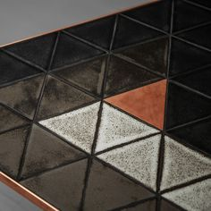 Detail of Penroso coffee, side table - triangle, ceramic tiles creates a unique, 3D illusion of the table top. Here shown in copper metal finish.