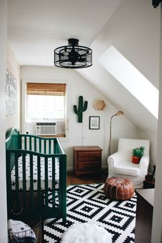 chambre bébé garçon sous pente avec ambiance bohème chic, lampadaire noir et lit nouveau-né en vert foncé, modèle de tapis blanc et noir à design géométrique
