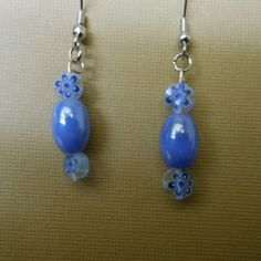 #jewelry Stainless steel hook earrings with a barrel shaped glass  blue-violet bead and  round acrylic discs with a blue flower design in them... Use the coupon code WEAREOPEN to save 10% on orders of $15 or more at checkout thru Sept 30th for our GRAND OPENING!.....